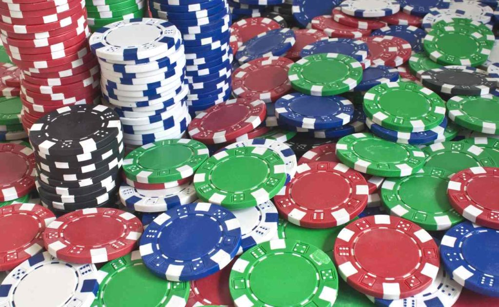 Various color poker chips stacked and scattered across a table