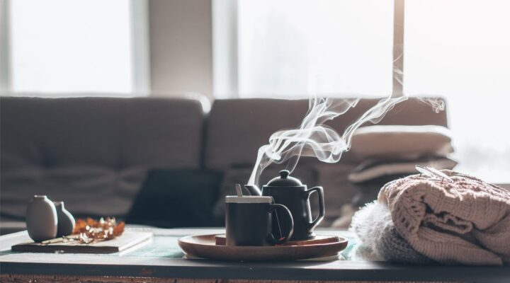 Sweaters and cup of tea with steam on a serving tray on a coffee table with couch in background