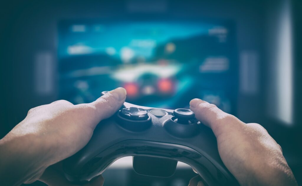 Hands holding console in front of large screen playing games