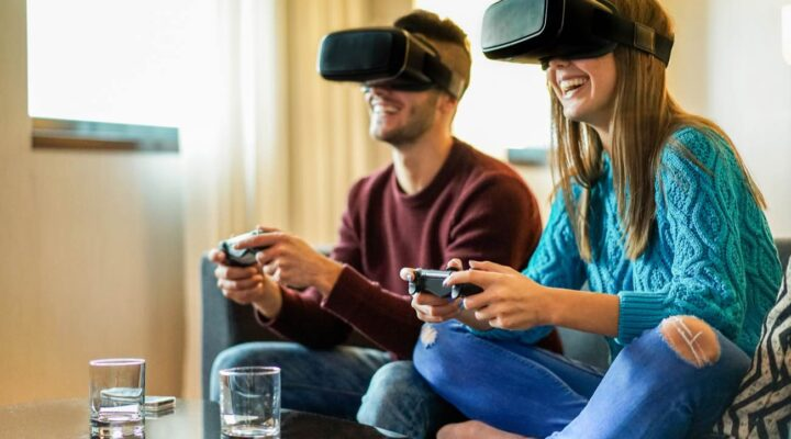 Couple playing video games wearing virtual reality glasses on the couch
