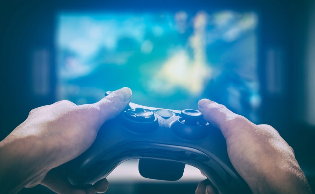 Gamer holding a video console playing on a large tv screen in the background