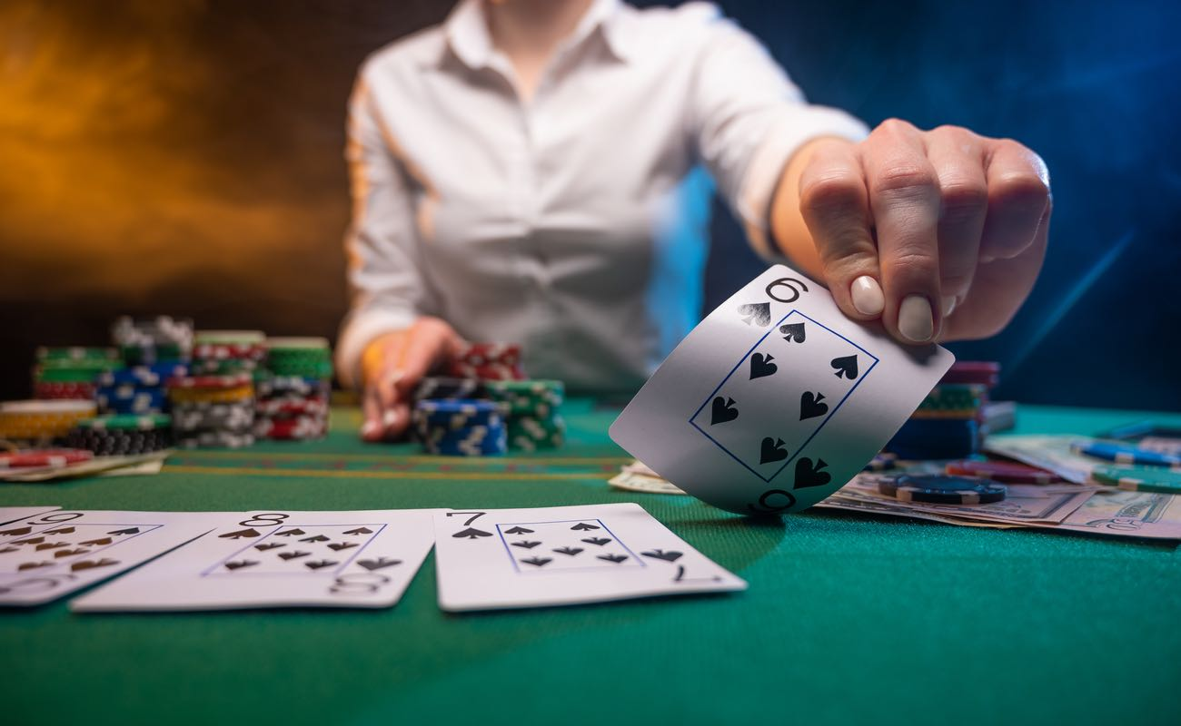 A croupier on a poker table holds up a six of spades