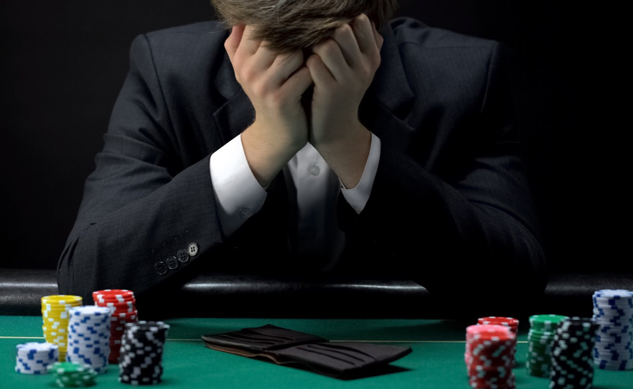 A man sits at a poker table with an empty wallet and his head in his hands