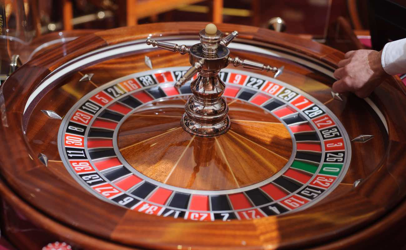A croupier holds the ball before the Roulette wheel is spun.