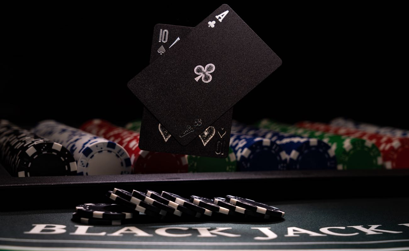 An ace of clubs and ten of spades float above a blackjack table.