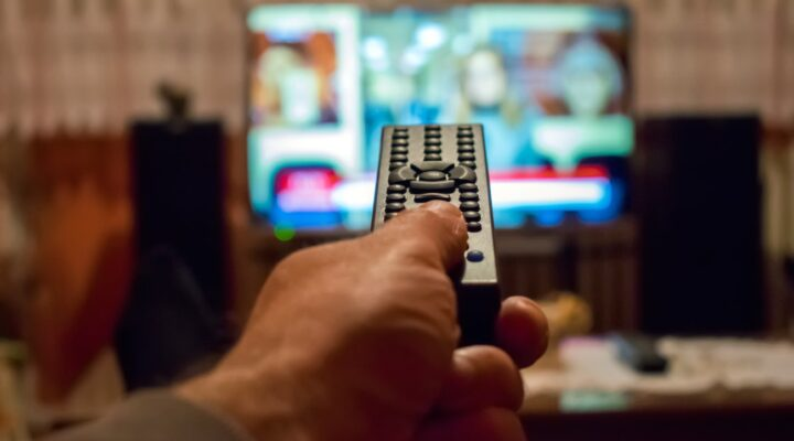 A thumb on a remote button with TV in the background