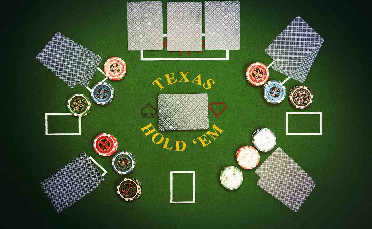 Texas Hold'em game played on green felt table with cards and poker chips