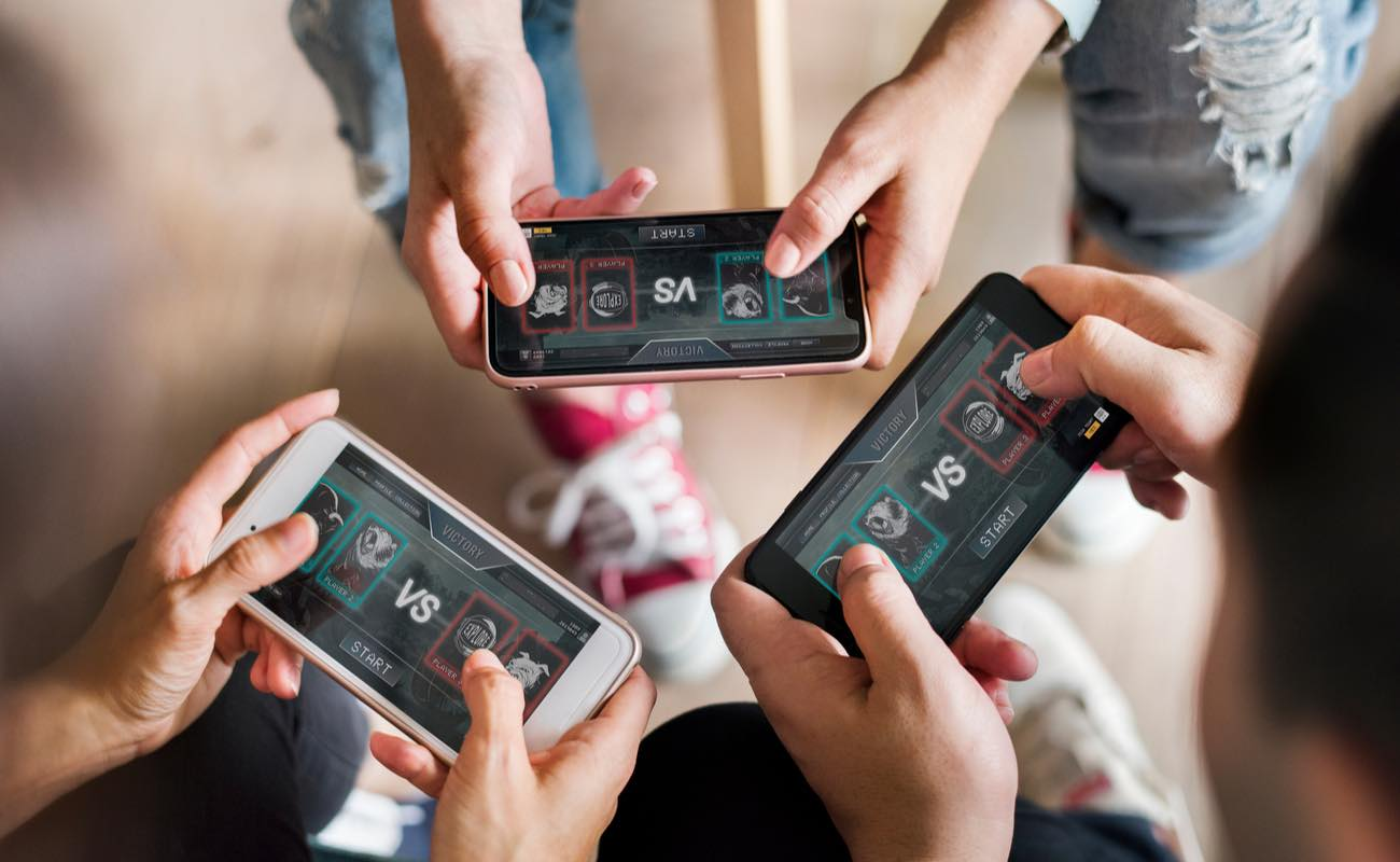 Aerial view of a group of friends playing a game on mobile phone