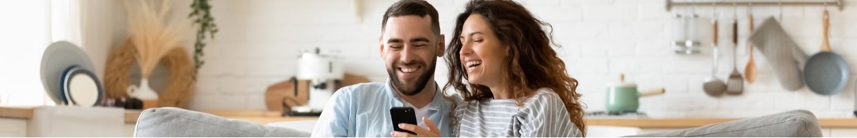 Happy couple sitting on the couch playing casino games on a smartphone