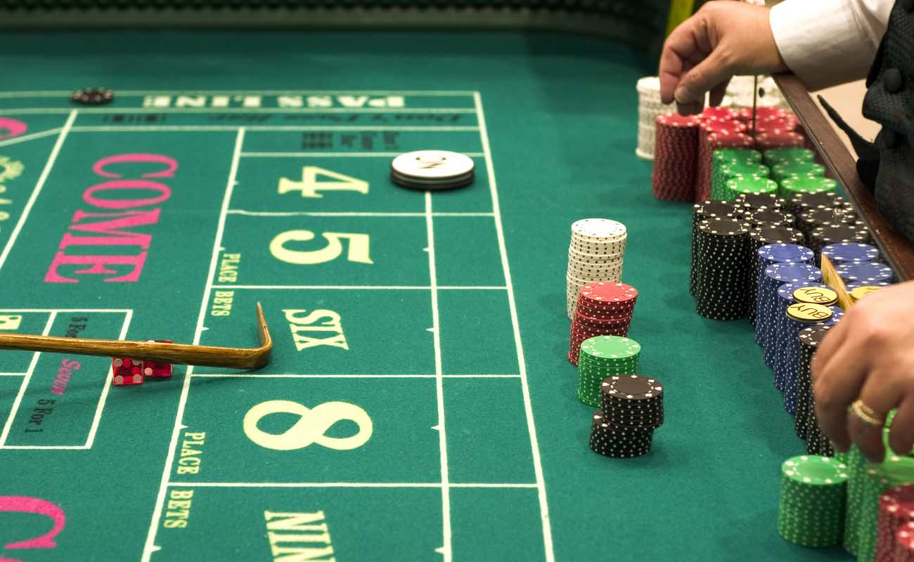 Closeup of a casino craps table with the croupier sorting casino chips