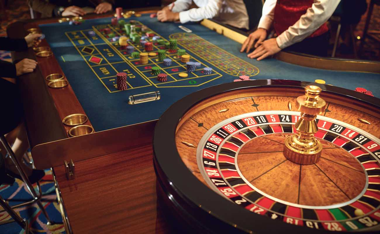 A roulette wheel and table in the background with croupier and players standing alongside