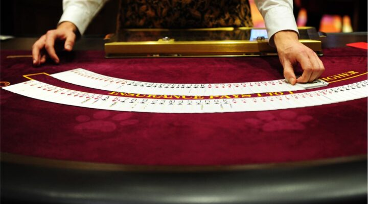 Croupier fans out playing cards on a casino table.