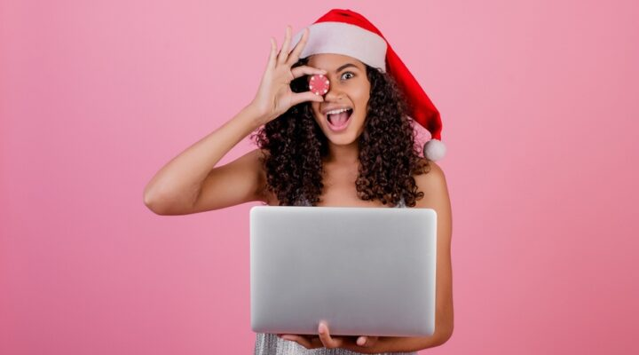 Woman with casino poker chip wearing holiday Santa hat isolated over pink background