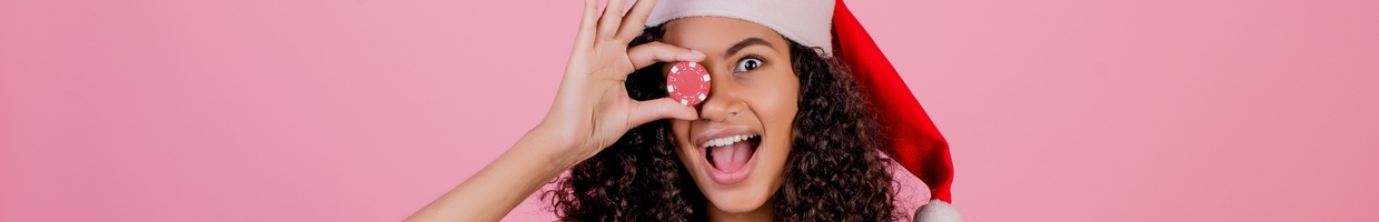 Woman with casino poker chip wearing holiday Santa hat and dress isolated over pink background.