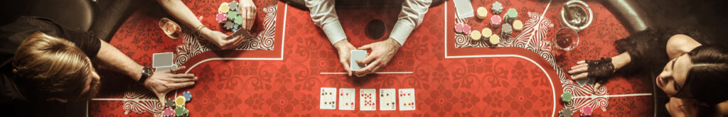 Players sit around a poker table with cards and chips.