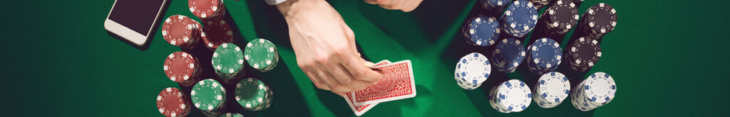 Hands holding cards with casino chips and a smartphone on a green casino table.