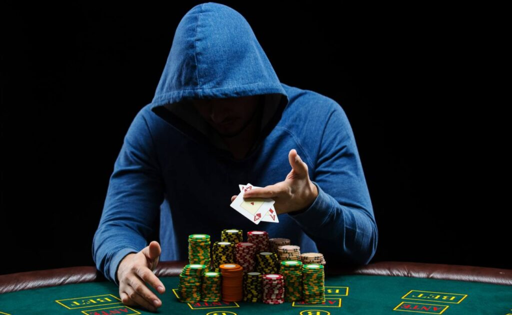 Man in a blue hoodie at a casino table showing a pair of aces with a large stack of casino chips.