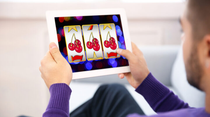 Man using a tablet to play online slot games.