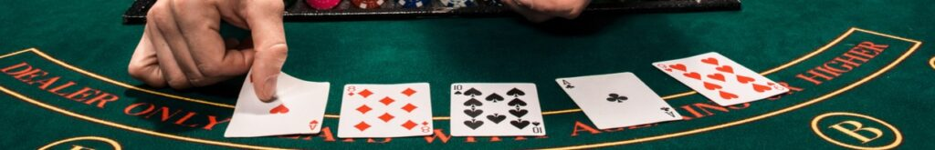 A dealer places cards face up on a green felt casino table.