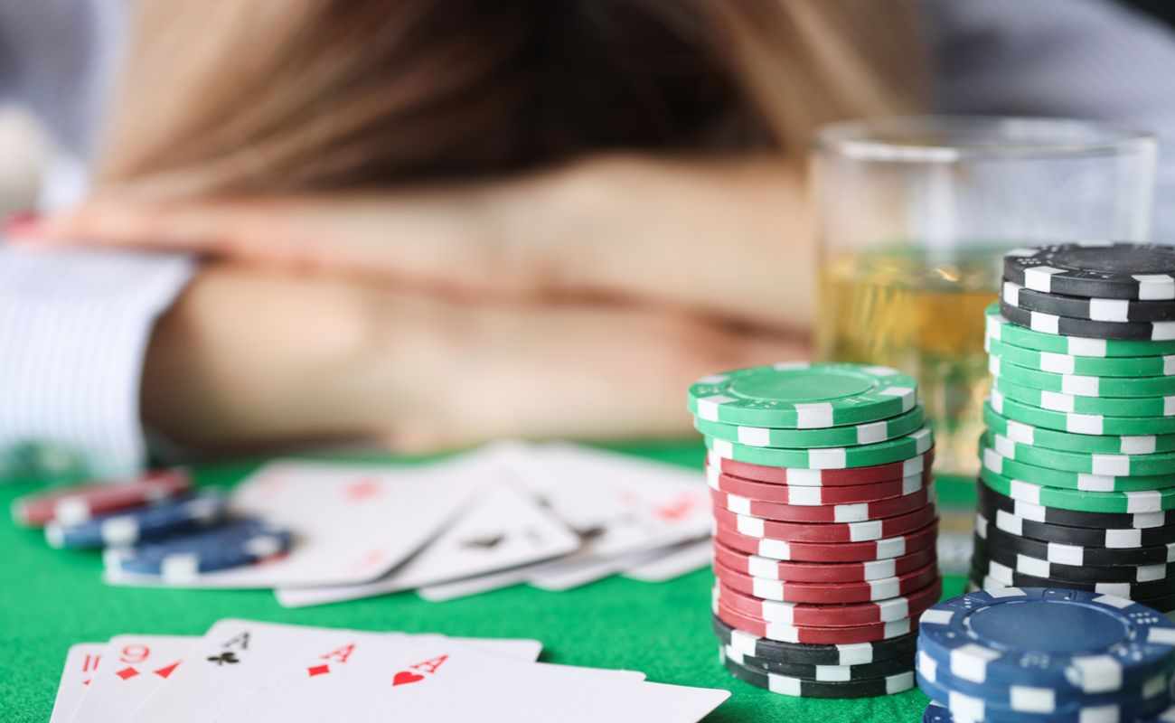 A woman lies on her arms on a casino table, an alcoholic drink and stacks of casino chips in front of her.