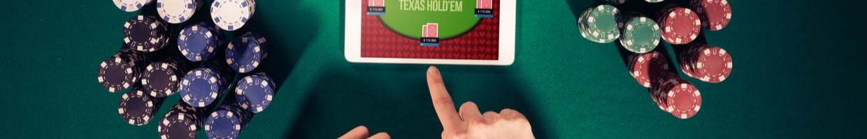 Poker player's hand with a tablet and stacks of casino chips on a green felt casino table.