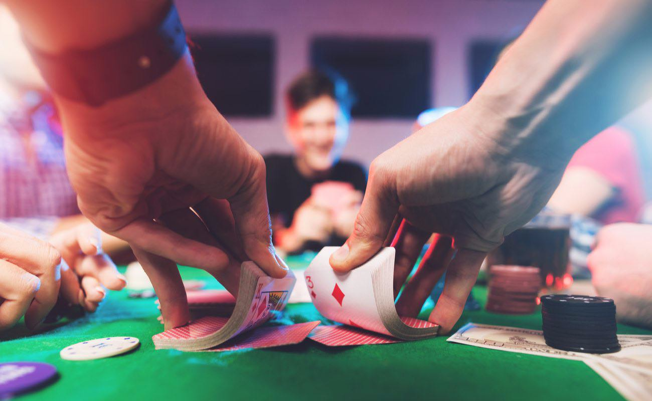 Hands shuffling a deck of cards with other players at a casino table with poker chips and cash scattered across the table.