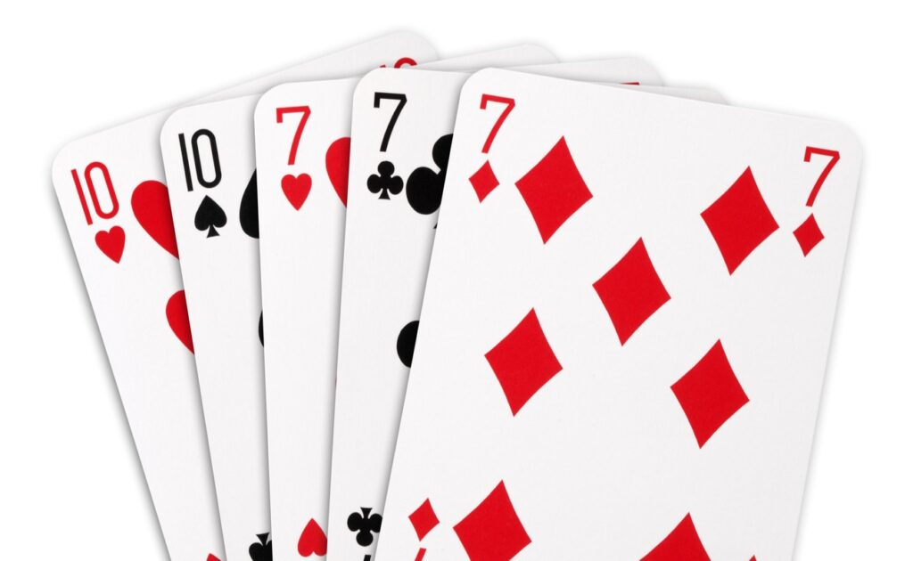 A full-house poker hand, consisting of two 10s and three sevens.