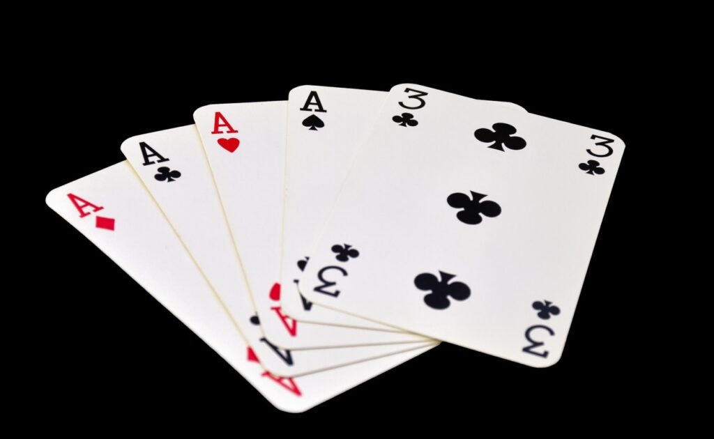 A four-of-a-kind poker hand with four aces and a three of clubs.