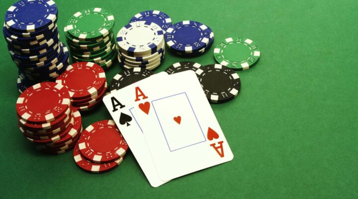 A pair of aces lies against a stack of casino chips on a green felt casino table.