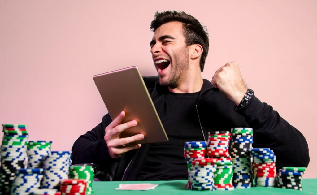 A happy poker player sitting behind stacks of casino chips wins a game of online poker on his tablet.