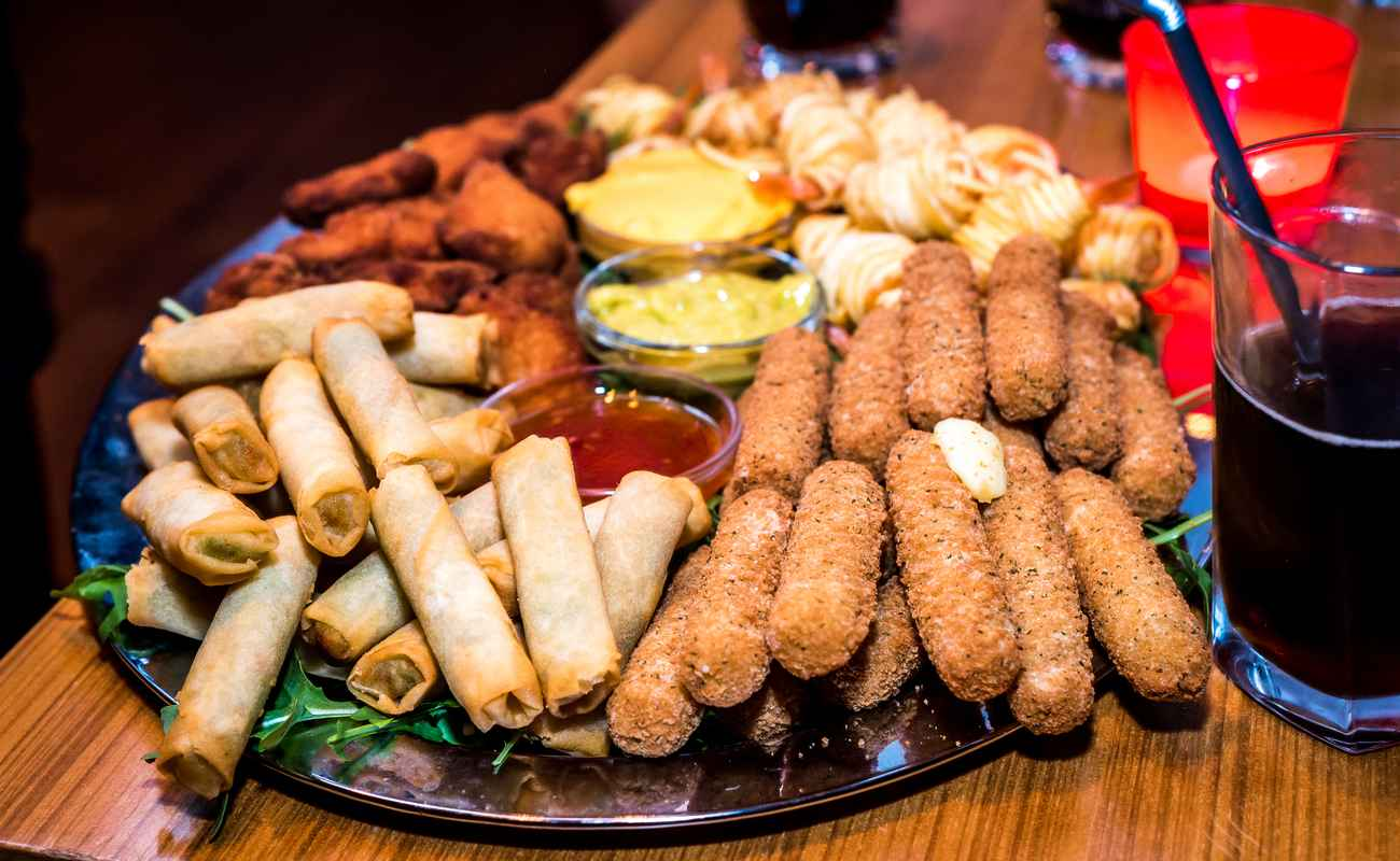 A platter of different finger foods sitting on a table with a drink.