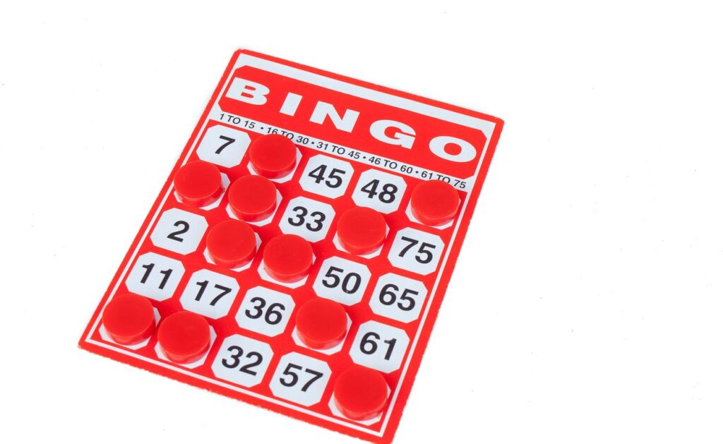 A red bingo card with red markers on some numbers.