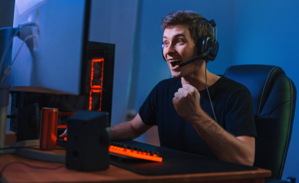 A young man celebrates while sitting at his gaming PC.