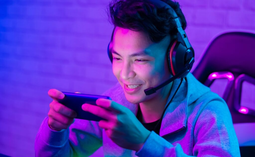 A gamer smiling and playing mobile games with purple lights.