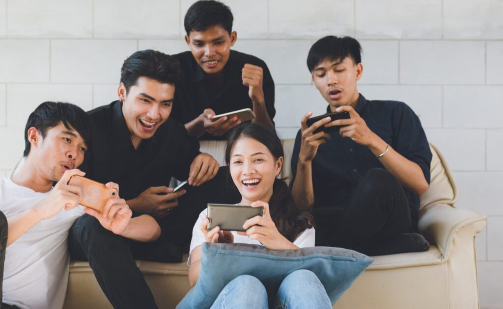 A group of friends enjoying themselves playing mobile games together.