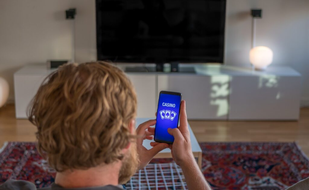 A man plays online casino games on his phone while sitting in front of a big TV.