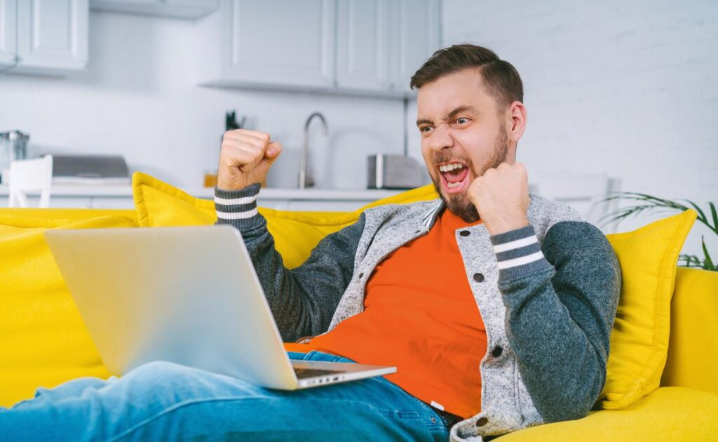 A young man celebrates a win at an online casino with a laptop on a yellow couch.