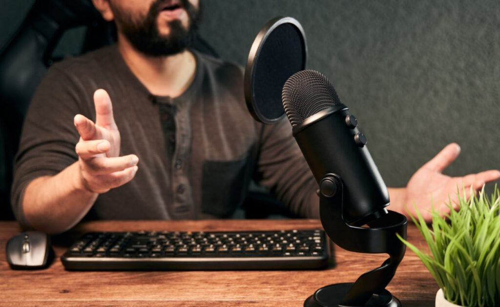 A man speaks into a dedicated desktop microphone with a pop filter.