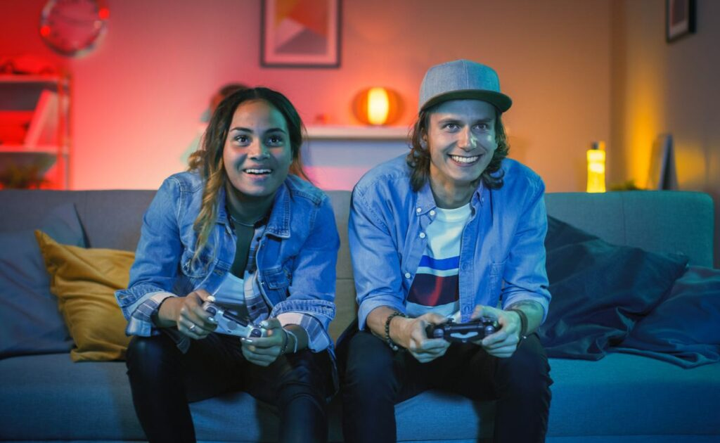 A young couple play video games in front of the TV.