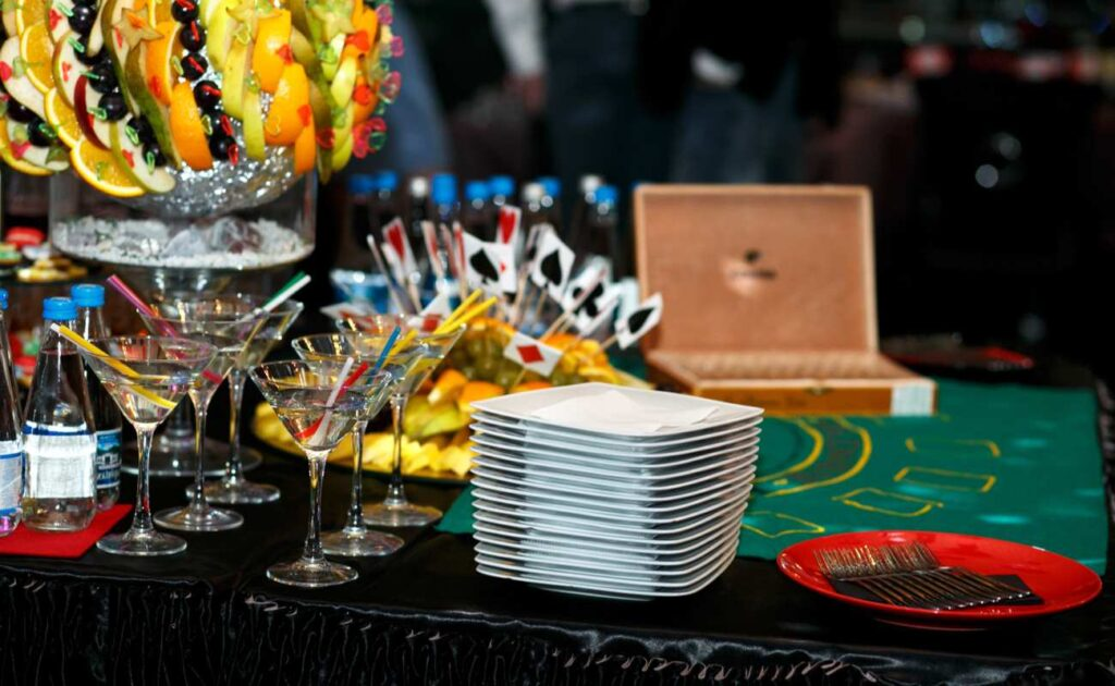 Platter of food with fruits and olives, with martini cocktails and plates on a casino table.