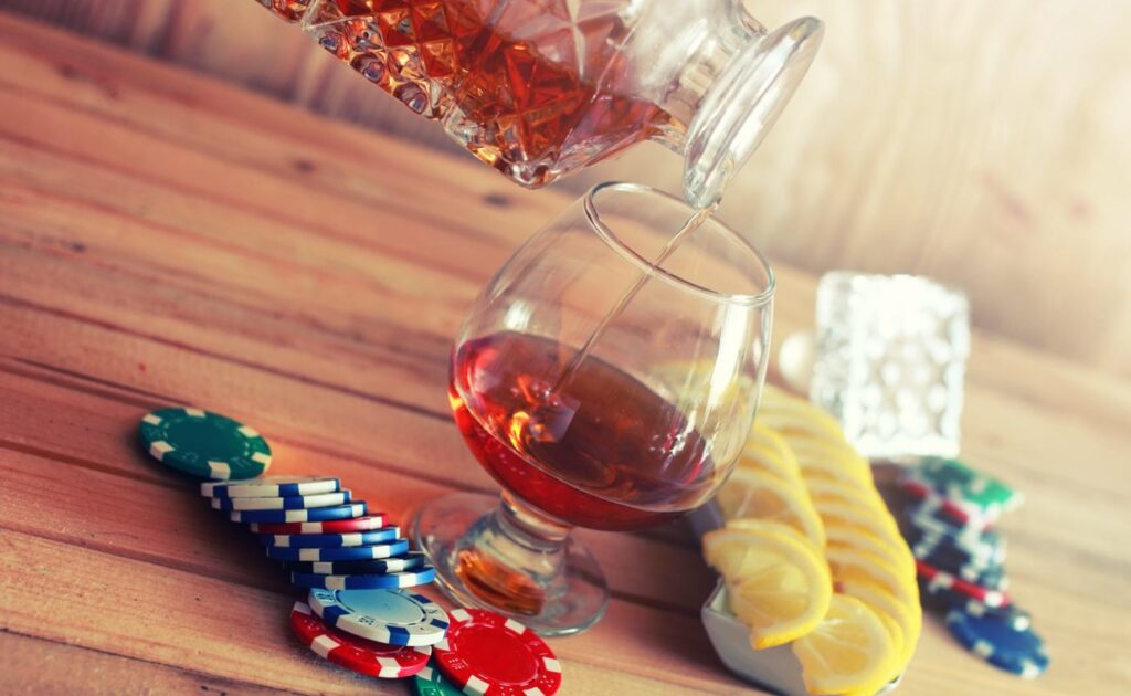 A drink being poured from a decanter into a glass with lemon slices and poker chips.