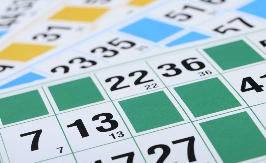 Close-up shot of three bingo cards with numbers and color blocks.