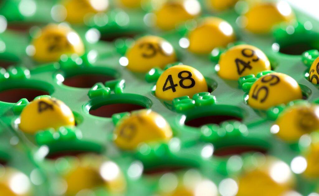Colorful bingo board filled with yellow bingo balls displaying numbers.