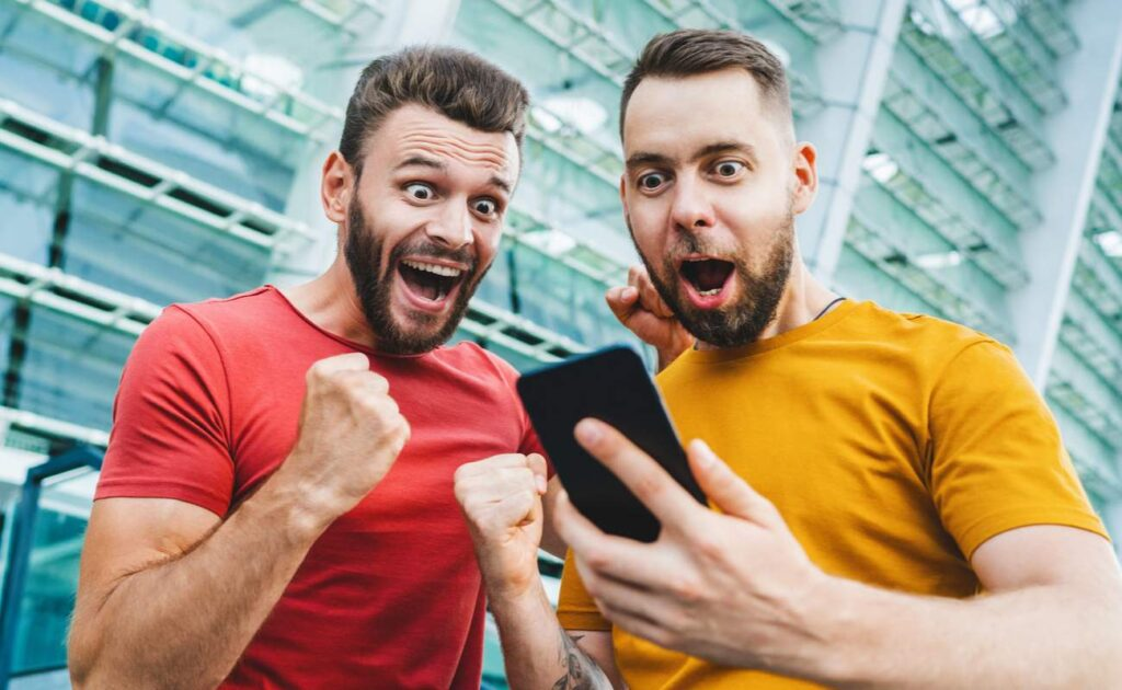 Two excited men celebrate an online gambling bet with a mobile device.