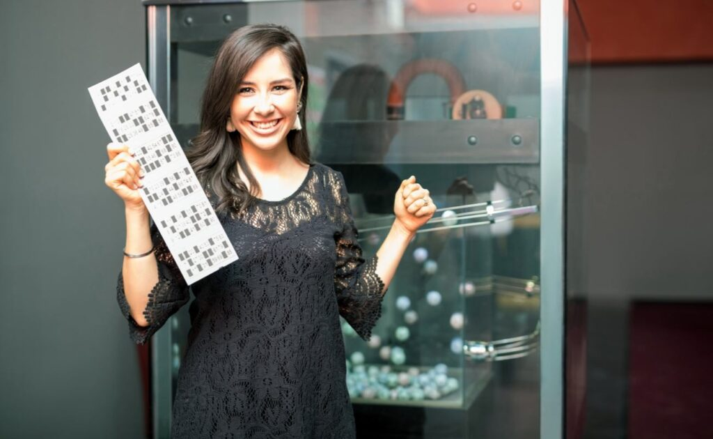A young woman holds up her bingo card in front of a bingo ball machine.