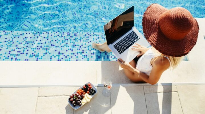 Woman using a laptop working remotely near a swimming pool.