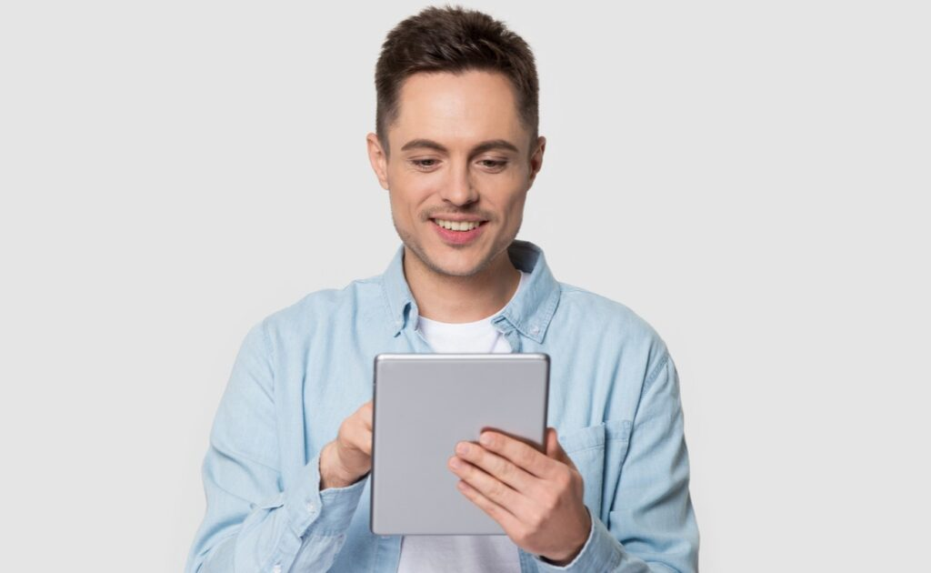 A young man plays online bingo on his tablet.