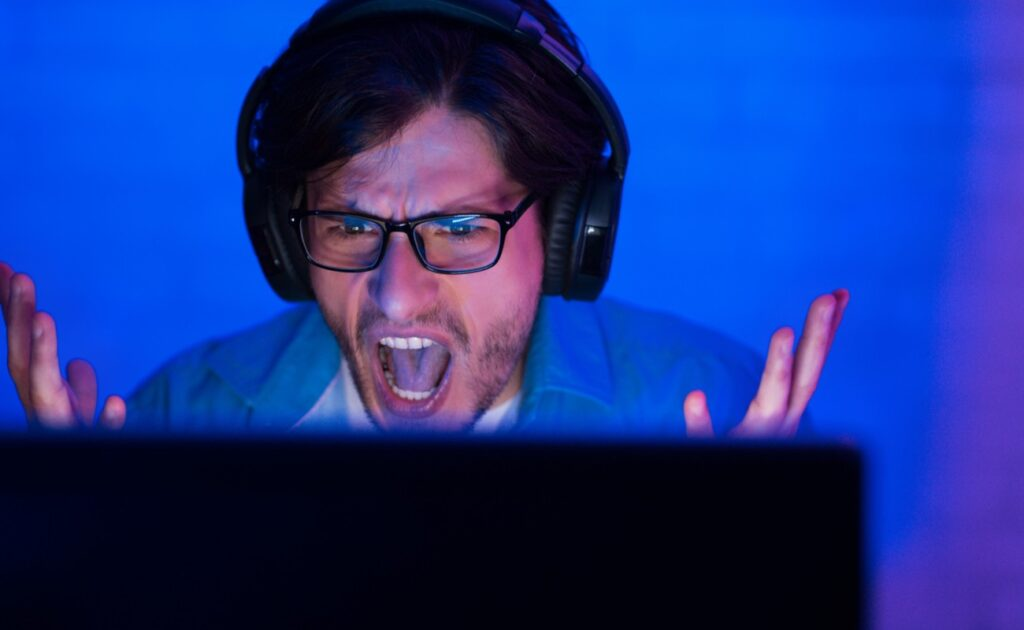 An angry player shouts at his computer screen.