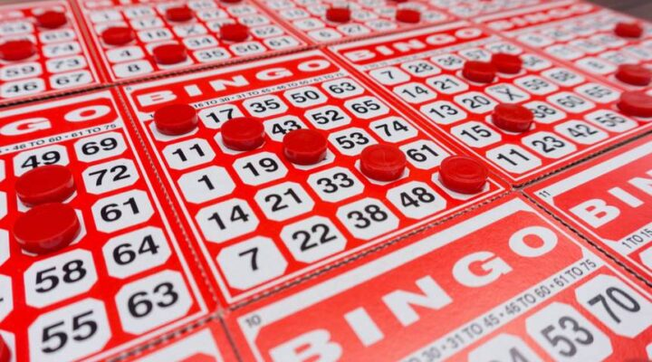 Several bingo cards with several numbers covered by bingo chips.