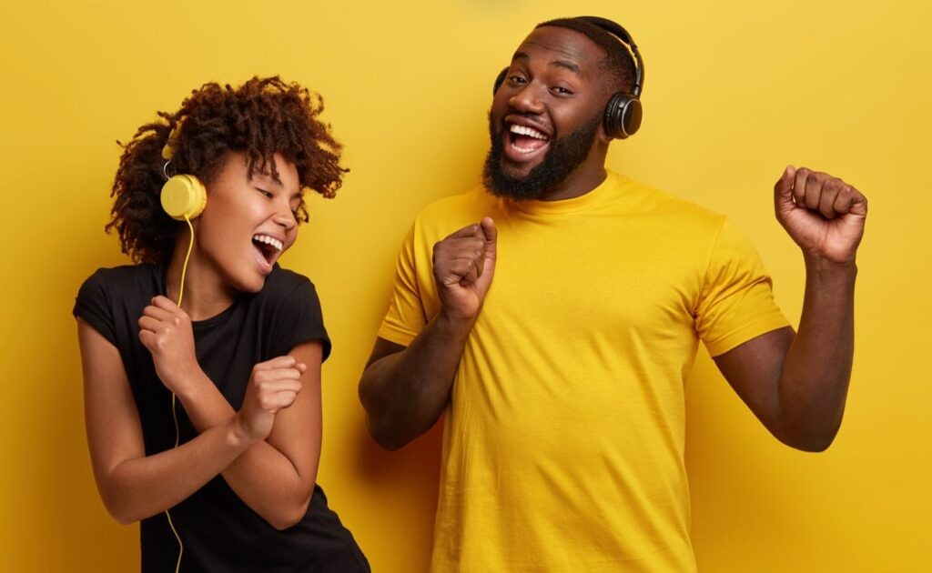Two cheerful young people listening to music and dancing against a yellow background.